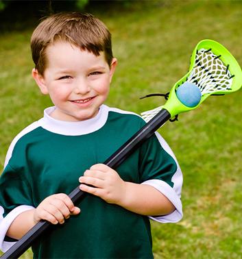 Lacrosse boy smiling racket ball 353x378 1