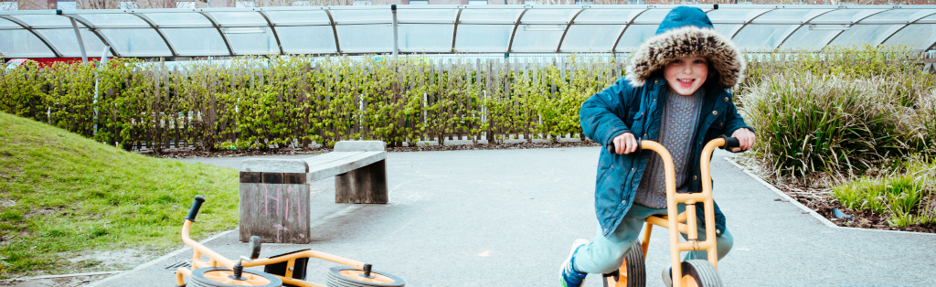 A boy having fun on a balance bike during a crucial break for play and outdoor learning.