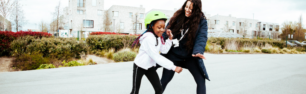 Young girl practices her rolling skating with a Premier Education Activity Professional.