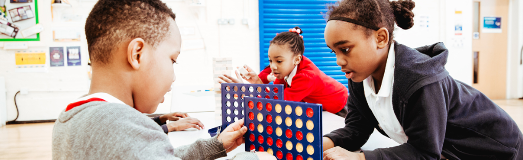 Children concentrating on a game of connect 4 during Premier Education Wraparound Care at their school in London.