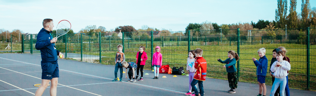 A Premier Education coach teaching children how to play tennis.
