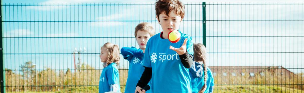 A child serving a tennis ball at a Premier Education activity course